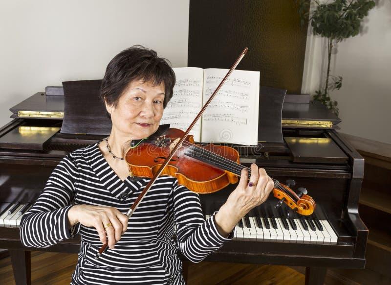 Ältere erwachsene Frauen, welche die Violine spielen lizenzfreies stockfoto