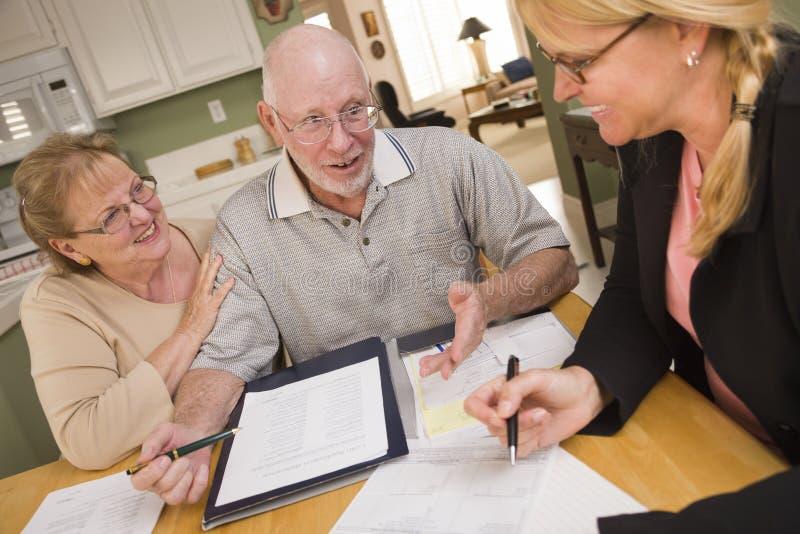 Ältere erwachsene Paare, die über Papiere in ihrem Haus mit Mittel hinausgehen stockbild