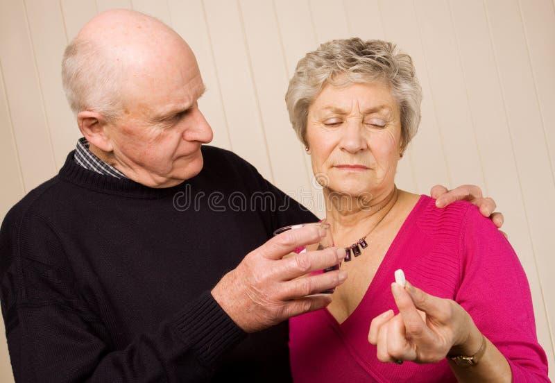 Ältere fällige Paare, die Schmerzmedikation nehmen stockfotos