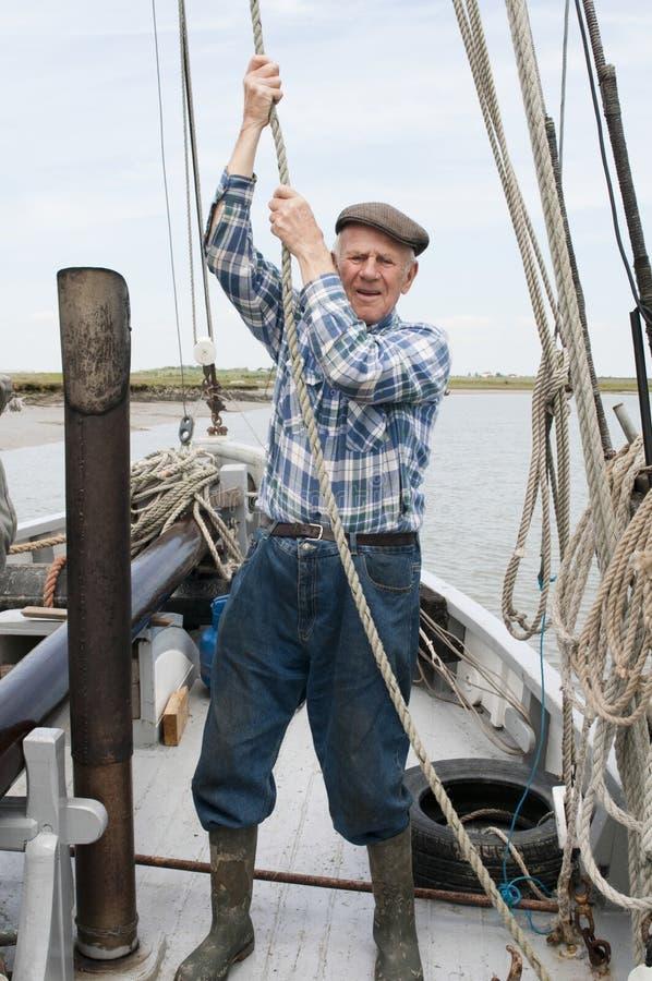 Ältere Fischer-Pulling Rope On-Plattform stockfotografie