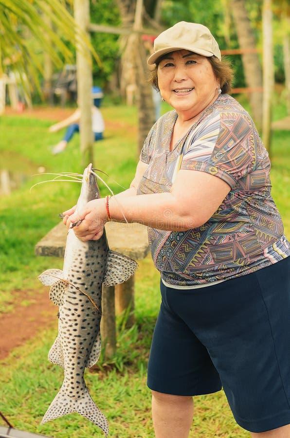 Ältere Fischerin, die einen Pintado-Fisch, schauend hält Vorwärts und lizenzfreies stockbild