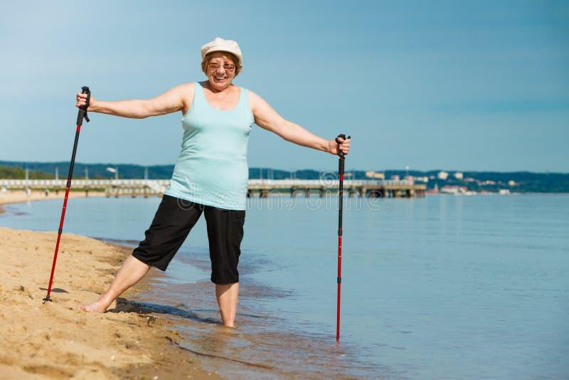 Ältere Frau übender Nordic, der auf Strand geht lizenzfreie stockfotos