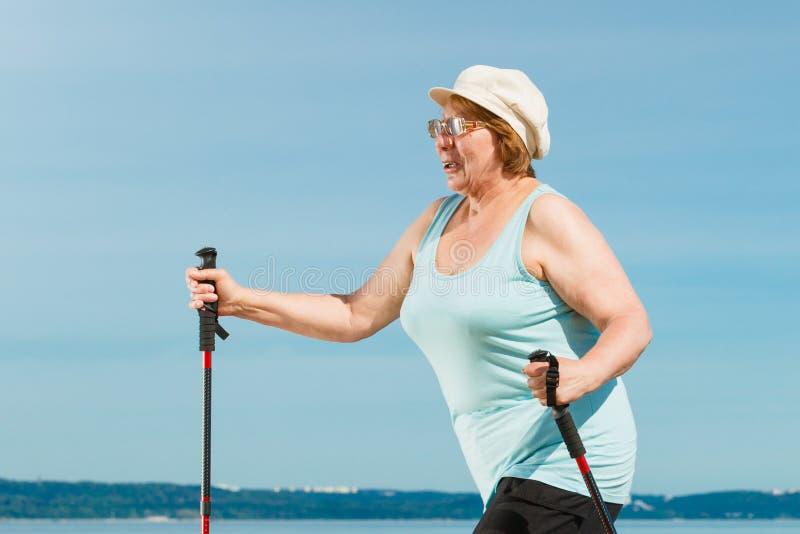 Ältere Frau übender Nordic, der auf Strand geht lizenzfreies stockfoto
