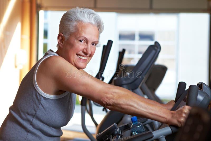 Ältere Frau auf spinnendem Fahrrad lizenzfreie stockfotos