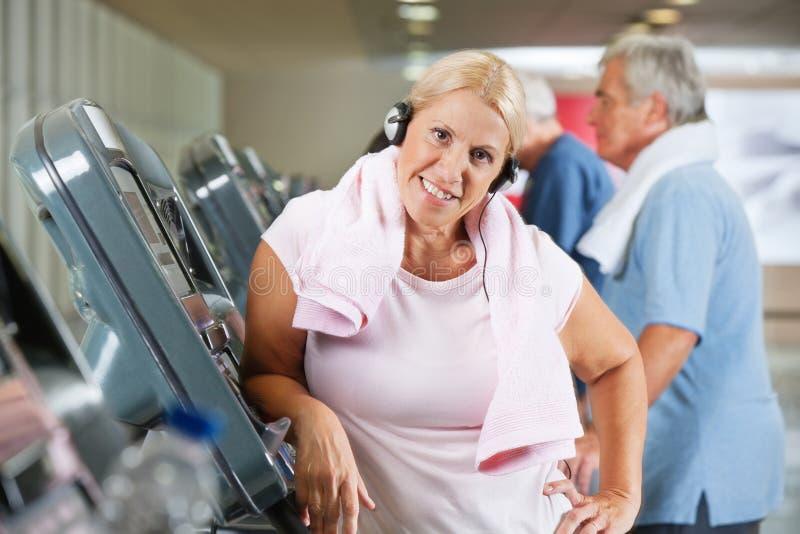Ältere Frau auf Tretmühle in der Gymnastik lizenzfreie stockfotos