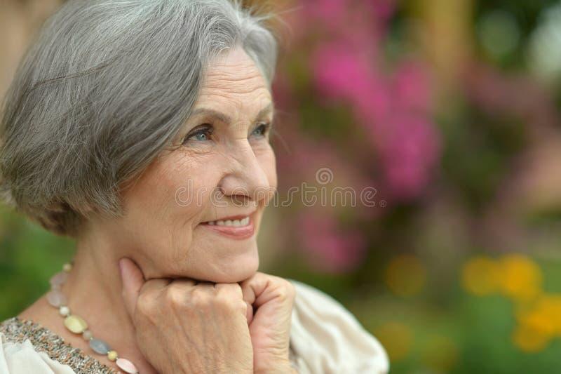 Ältere Frau auf Weg mit rosa Blumen lizenzfreie stockbilder