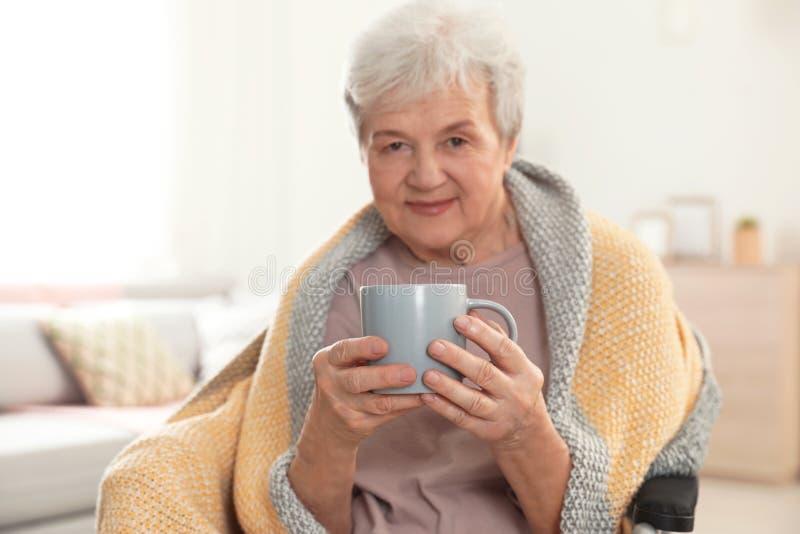 Ältere Frau bedeckt mit umfassendem trinkendem Tee am Pflegeheim stockbilder