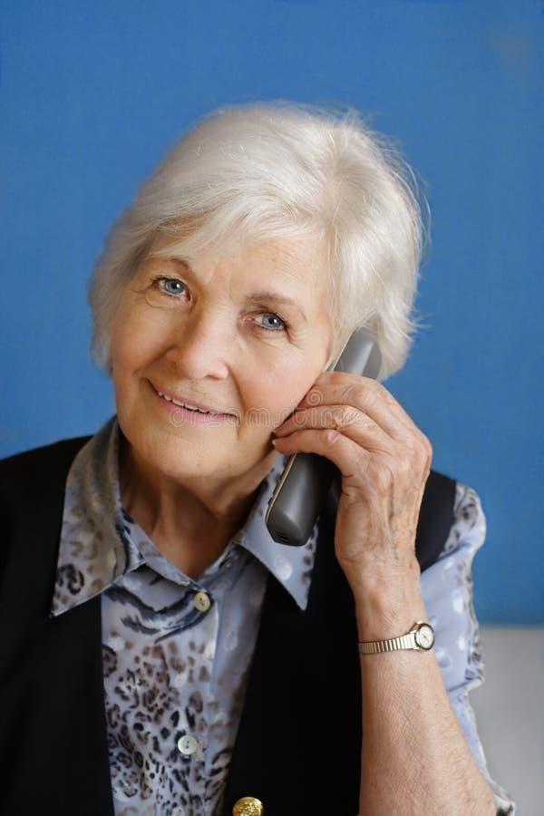 Ältere Frau besetzt am Telefon lizenzfreies stockfoto