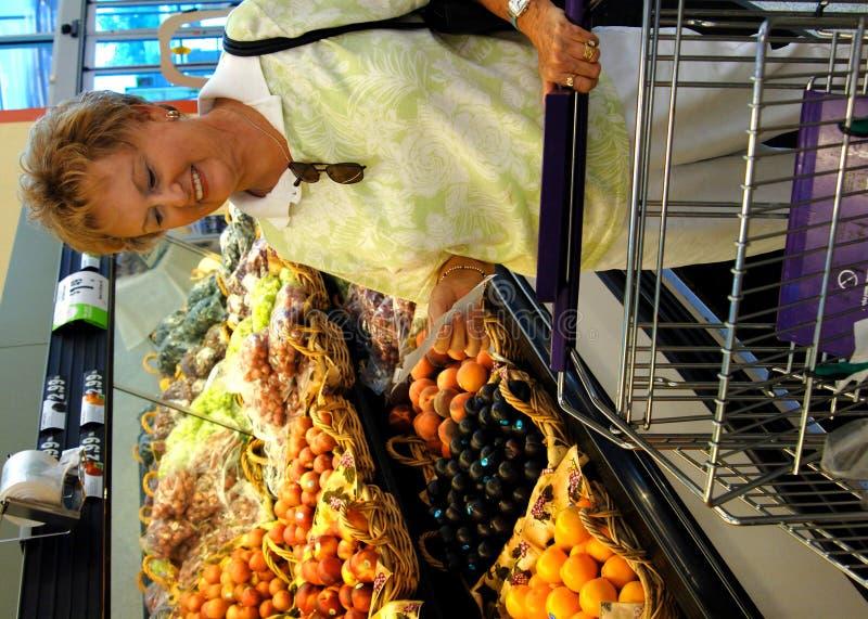 Ältere Frau in den Gemischtwarenladen stockbild