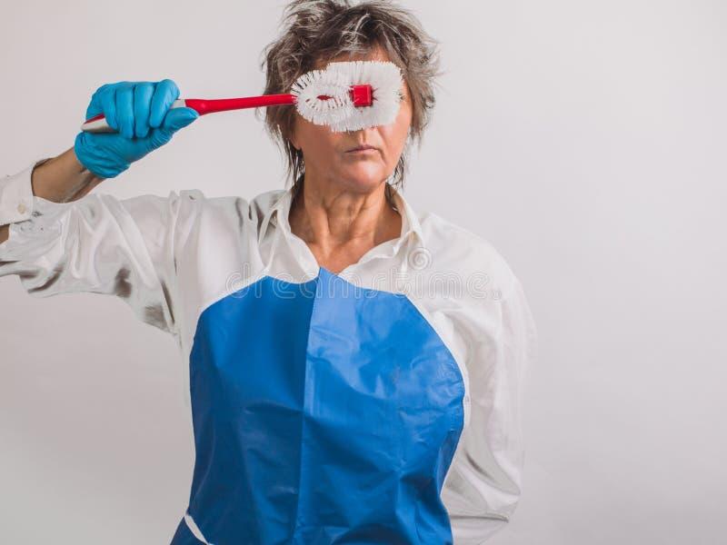 Ältere Frau in den schützenden Gummihandschuhen und Schutzblech mit einem Rot lizenzfreies stockbild