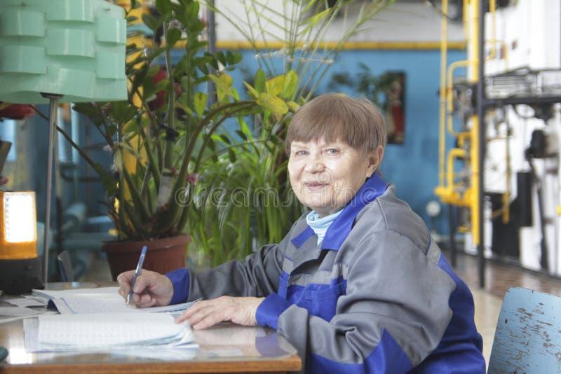 Ältere Frau in der Arbeitskleidung schreibt auf Arbeitsplatz lizenzfreie stockfotografie