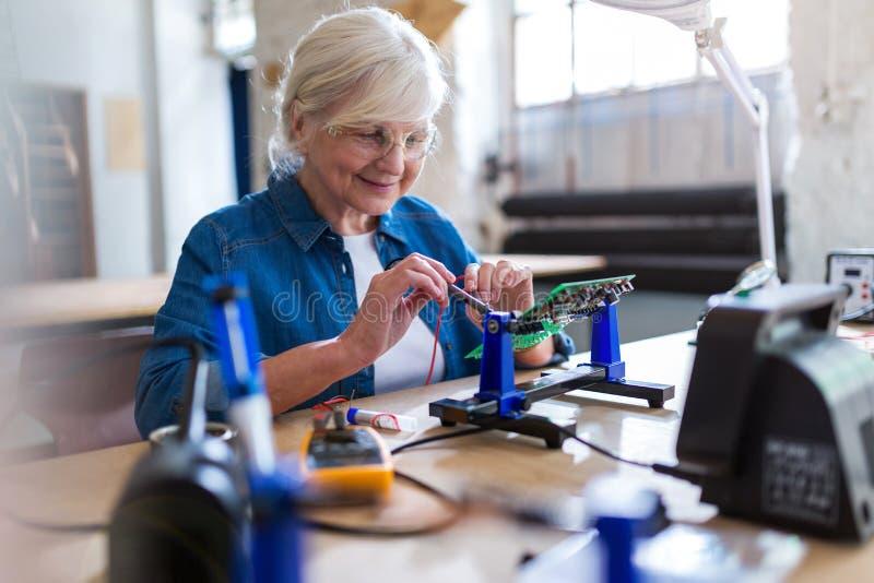 Ältere Frau in der Elektronikwerkstatt stockbild