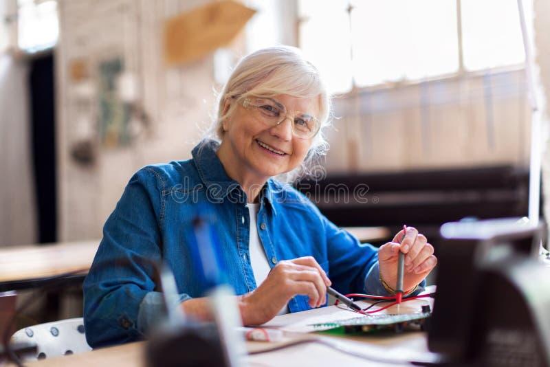 Ältere Frau in der Elektronikwerkstatt lizenzfreie stockfotos