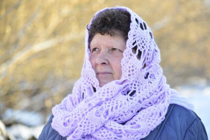 Ältere Frau in der Flieder strickte Schal auf ihrem Kopf stockbilder