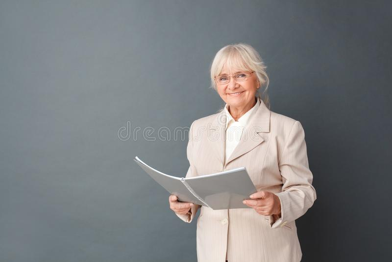 Ältere Frau in der fromal Klagen- und Glasstudiostellung lokalisiert auf Grau mit dem Notizbuch, das positive Planung der Kamera  stockbilder