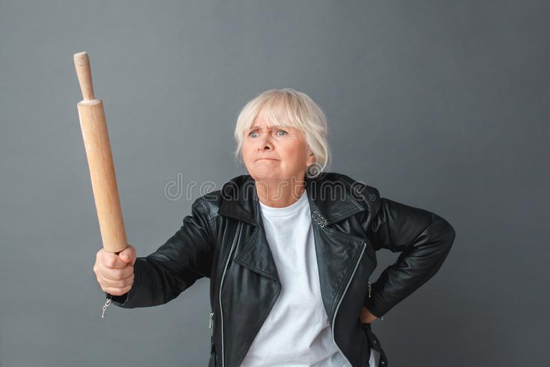 Ältere Frau in der Lederjackestudiostellung lokalisiert auf Grau mit dem Nudelholz, das jemand verärgert bedroht stockfotografie