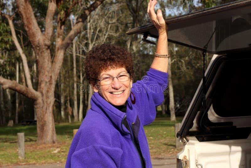 Ältere Frau an der Rückseite des Autos stockbild
