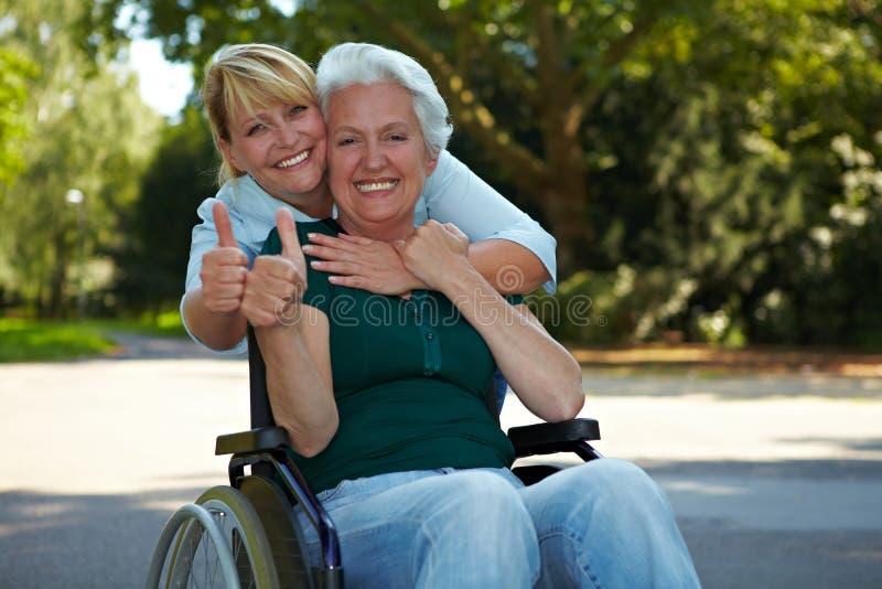 Ältere Frau in der Rollstuhlholding lizenzfreie stockfotos