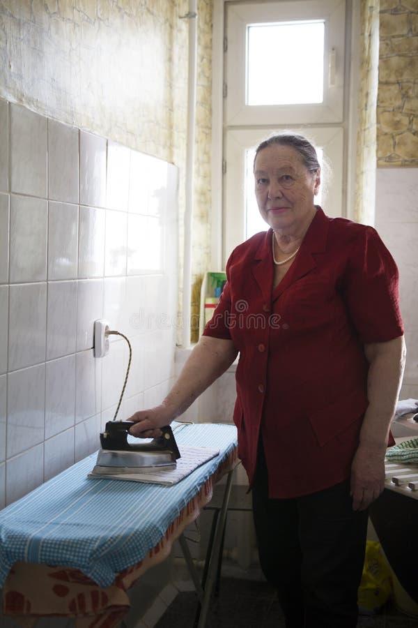 Ältere Frau in der roten Bluse ein Tuch zu Hause bügelnd lizenzfreies stockfoto