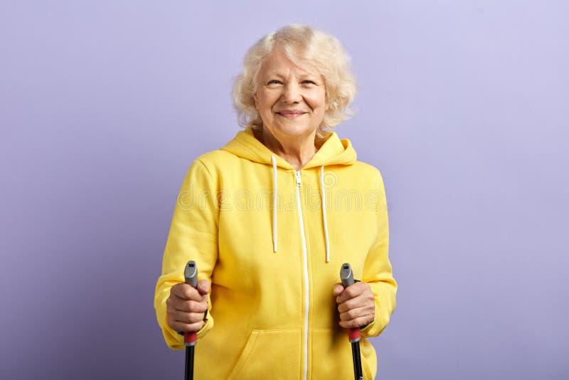 ?ltere Frau in der Sportkleidung, die mit nordischen Wanderst?cken im purpurroten Studio steht stockbild