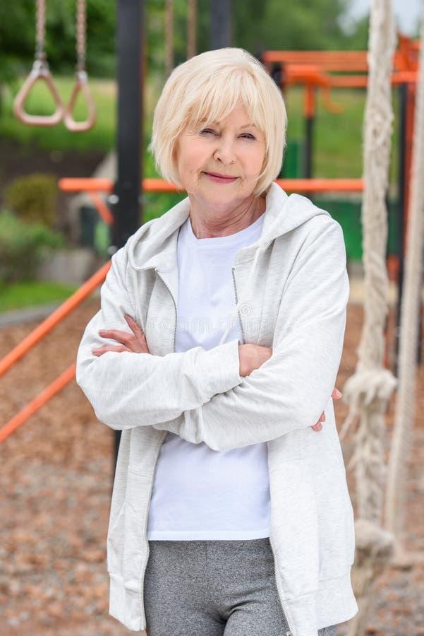 ältere Frau in der Sportkleidung mit der gekreuzten Arm-Stellung stockfotografie