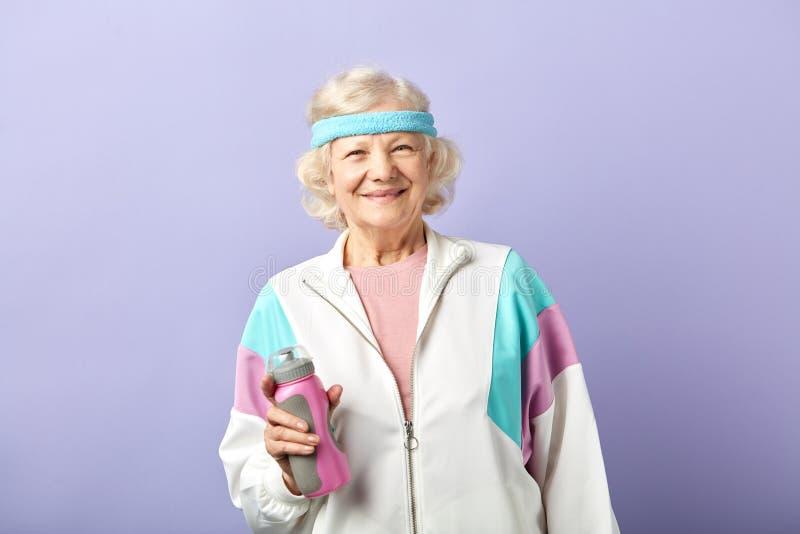 ?ltere Frau in der Sportkleidung mit Wasserflasche l?chelnd und auf Purpur tanzend stockfotografie