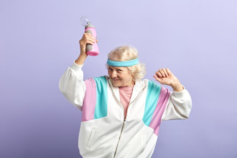 ?ltere Frau in der Sportkleidung mit Wasserflasche l?chelnd und tanzend lokalisiert auf Purpur stockbilder