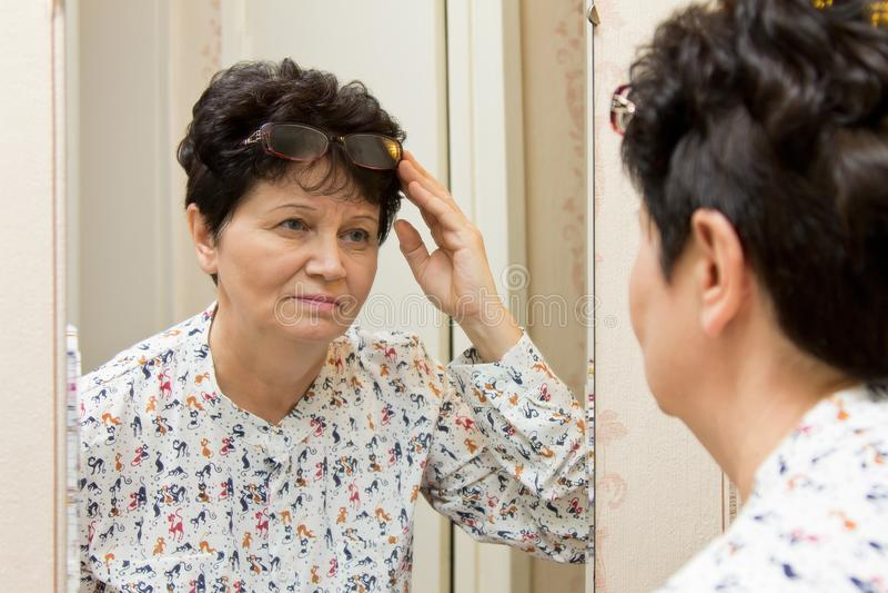 Ältere Frau des Brunette, die Brillen auf die Oberseite ihres Kopfes hält und penibel im Spiegel betrachtet stockfotografie