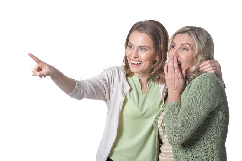 Ältere Frau des Porträts mit der Tochter, die auf weißen Hintergrund zeigt lizenzfreie stockfotos