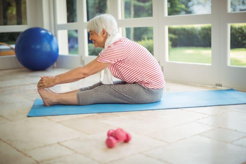 Ältere Frau, die Übung zu Hause ausdehnend durchführt stockfotos
