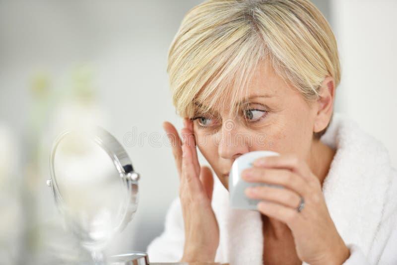 Ältere Frau, die Antialterncreme auf ihrer Haut aufträgt stockbild