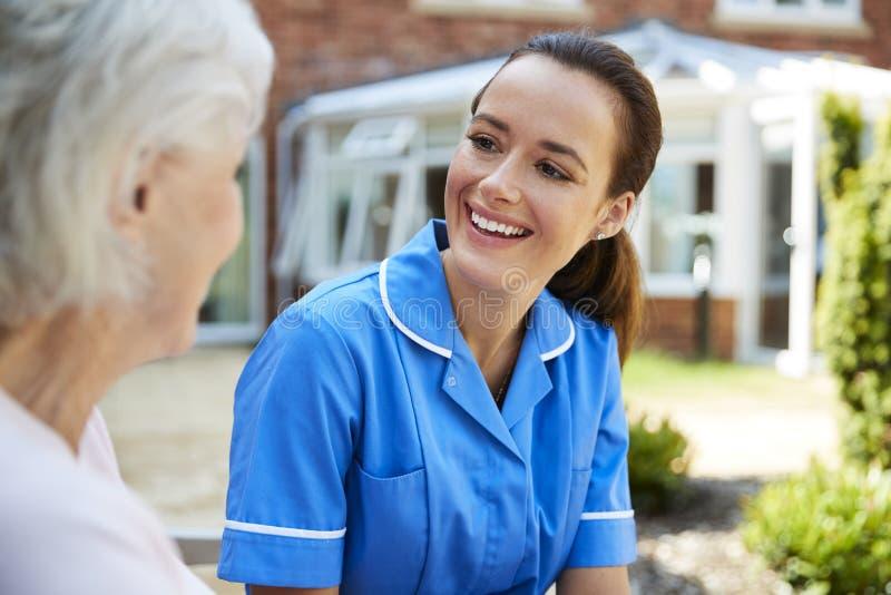 Ältere Frau, die auf Bank sitzt und mit Krankenschwester In Retirement Home spricht lizenzfreies stockbild