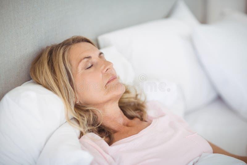 Ältere Frau, die auf Bett schläft lizenzfreie stockfotos