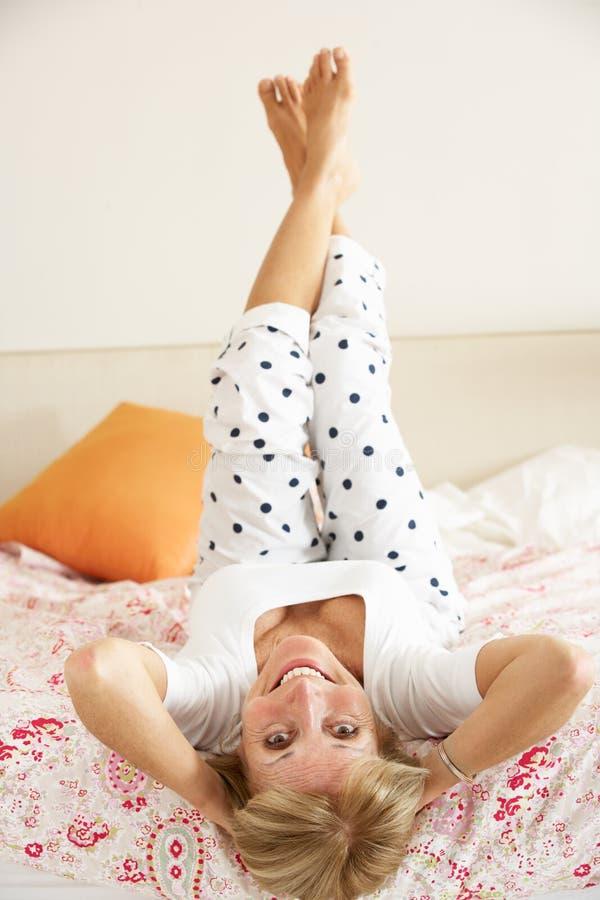 Ältere Frau, die auf Bett sich entspannt lizenzfreies stockbild