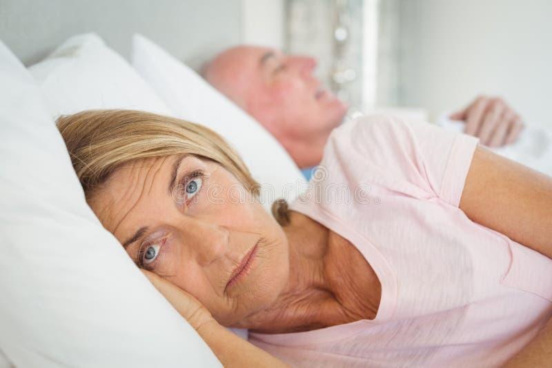 Ältere Frau, die auf Bett stillsteht lizenzfreies stockfoto