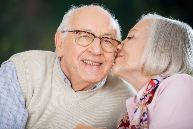 Ältere Frau, die auf der Backe des Mannes küsst stockbild