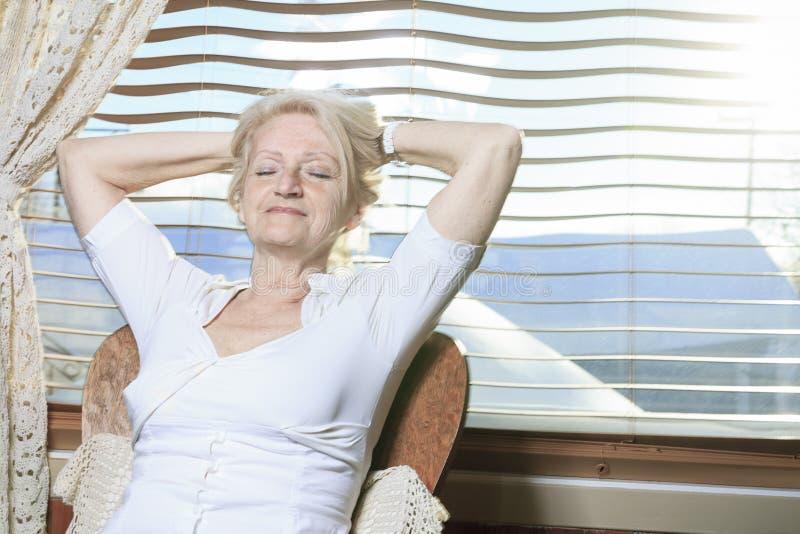 Ältere Frau, die auf der Küche sich entspannt stockfotografie