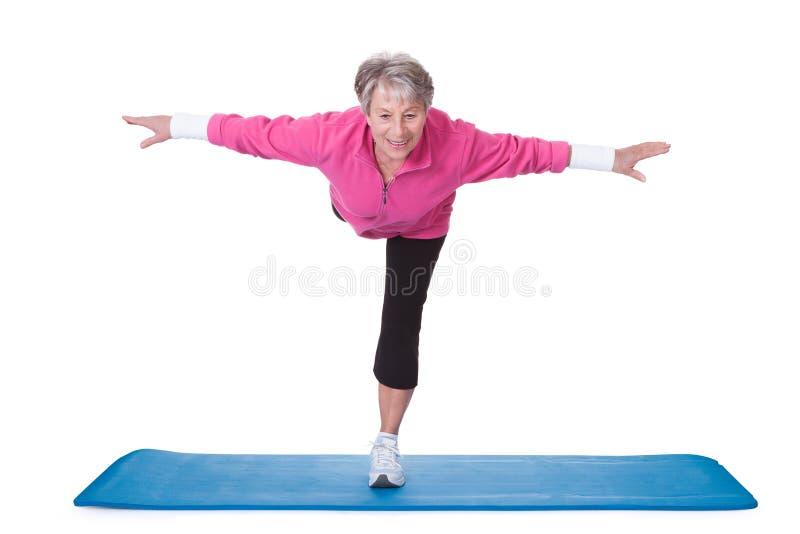 Ältere Frau, die auf einem Bein und Trainieren steht stockbild
