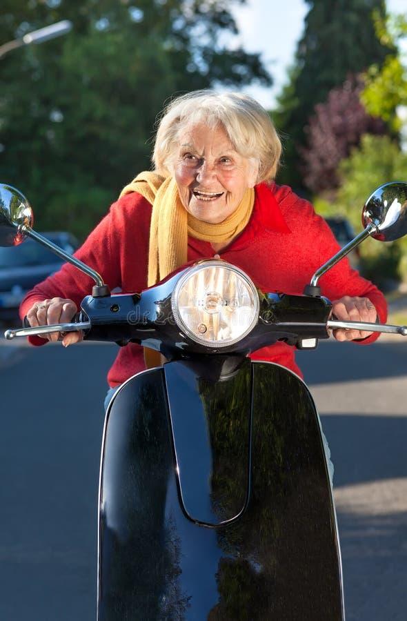 Ältere Frau, die auf einen Roller beschleunigt stockbild