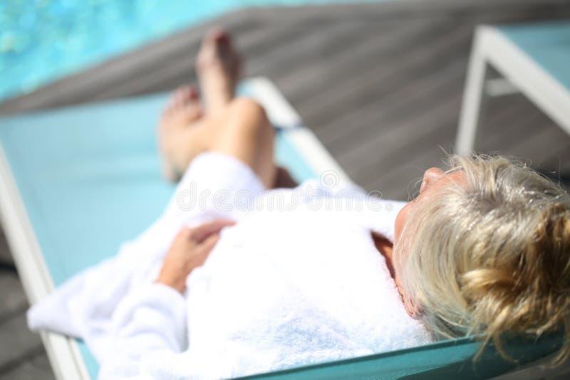 Ältere Frau, die auf langem Stuhl sich entspannt lizenzfreie stockbilder