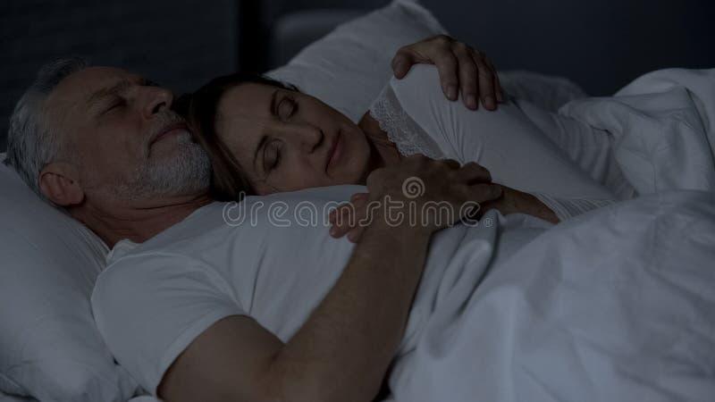 Ältere Frau, die auf männlichem Kasten, Paar schläft im Bett, Mann umarmt sie liegt stockbild