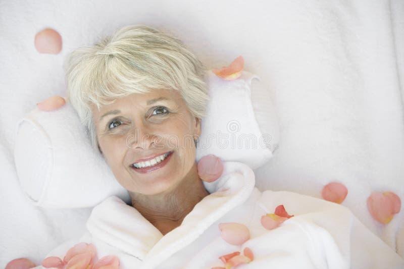 Ältere Frau, die auf Massage-Bett liegt lizenzfreies stockbild