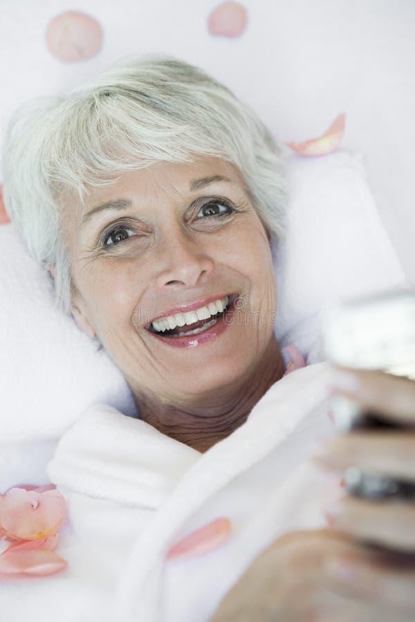 Ältere Frau, die auf Massage-Tabelle am Badekurort liegt stockfotos