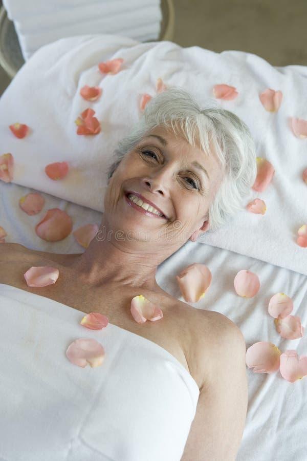 Ältere Frau, die auf Massage-Tabelle liegt stockfoto