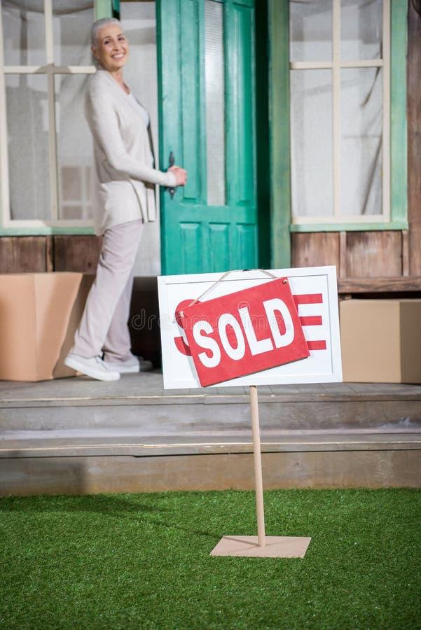 Ältere Frau, die auf Portal des neuen Hauses mit Verkaufszeichen steht stockfotografie
