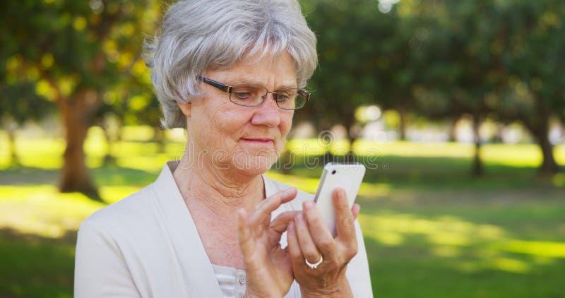 Ältere Frau, die auf Smartphone am Park simst stockbild