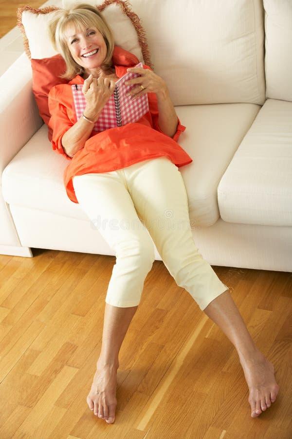 Ältere Frau, die auf Sofa-Lesetagebuch sitzt lizenzfreies stockbild