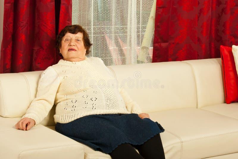 Ältere Frau, die auf Sofa sich entspannt stockbild