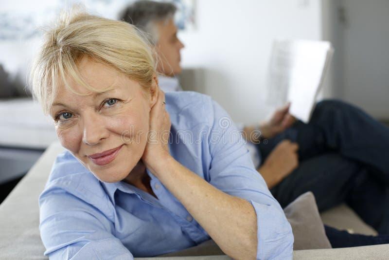 Ältere Frau, die auf Sofa sitzt lizenzfreies stockbild