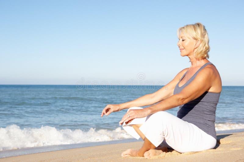 Ältere Frau, die auf Strand meditiert lizenzfreie stockfotos